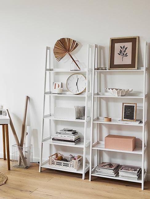 horloge murale blanche posée sur une grande étagère blanche avec objets déco