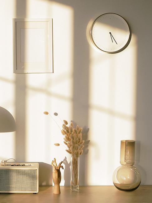 Horloge murale blanche accroché sur un mur blanc, avec déco boho et herebe de pampa