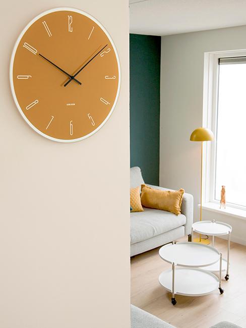 horloge murale jaune accrochée sur un mur blanc