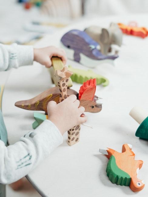 Enfant jouant avec des figurines en bois peintes