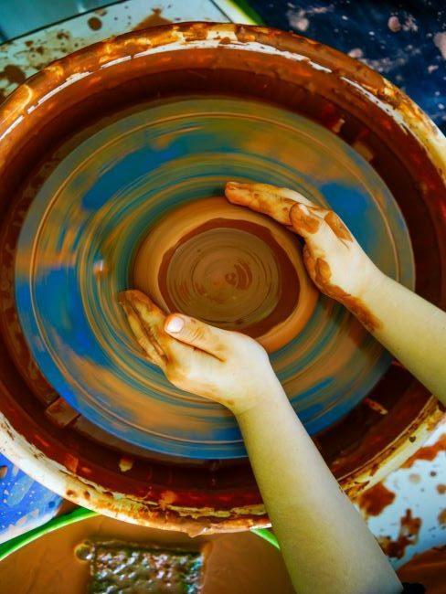 Mains d'enfant faisant de la poterie