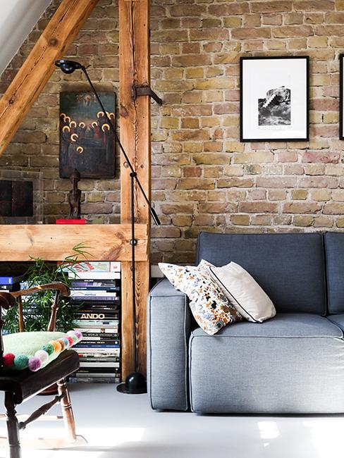 salon avec mur en brique, poutres en bois et canapé gris