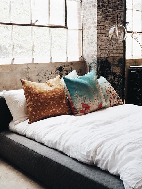 chambre industrielle avec lit et mur en brique