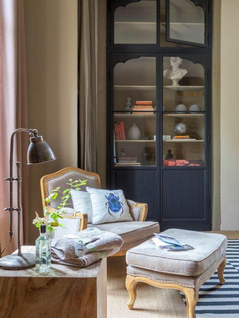 Salon vintage avec fauteuil et repose-pieds crème avec vitrine bleue foncé