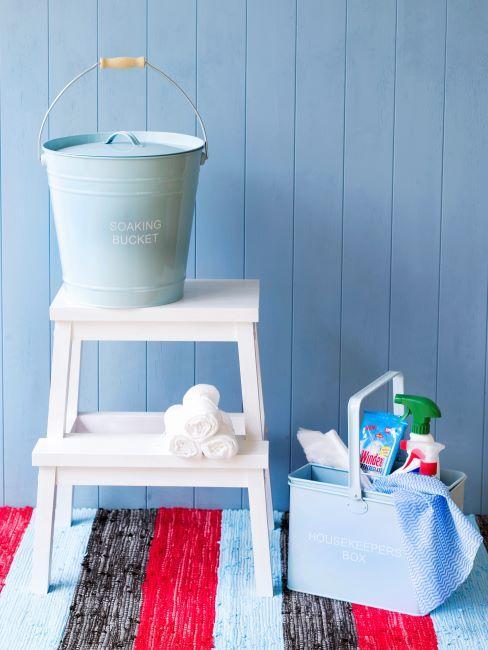 Mur bleu, tapis rayé, tabouret blanc et accessoires de nettoyage