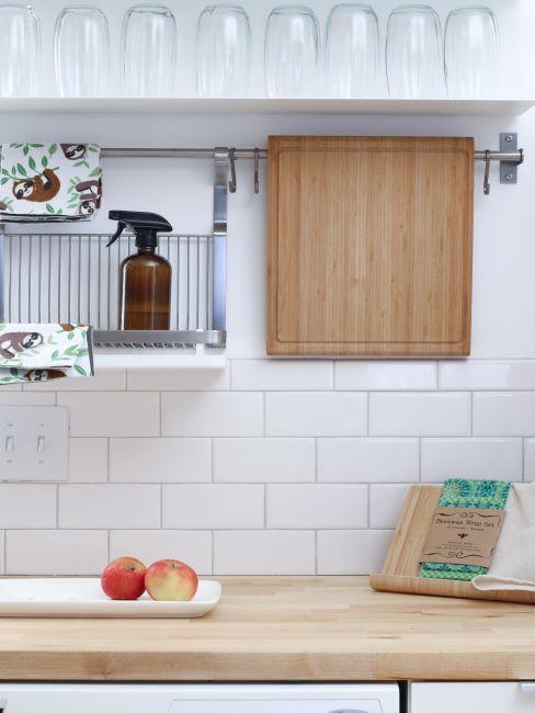 Comptoir de cuisine en bois, carrelage blanc, planche à découper en bois et verres à eau