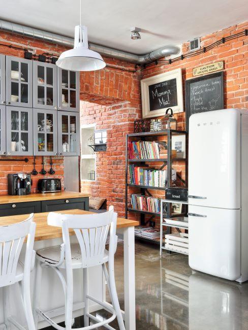 Cuisine avec mur de brique apparente, frigo et blanc, table et chaises en bois