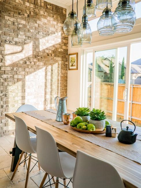 Salle à manger avec table en bois massif, chaises en plastique, suspensions en verre et mur en brique