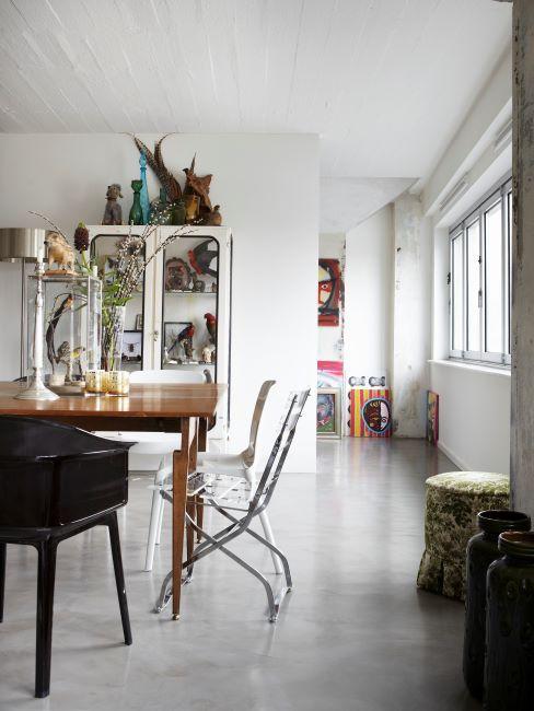 Buffet en bois blanc dans une salle à manger avec table en bois massif et chaises diverses