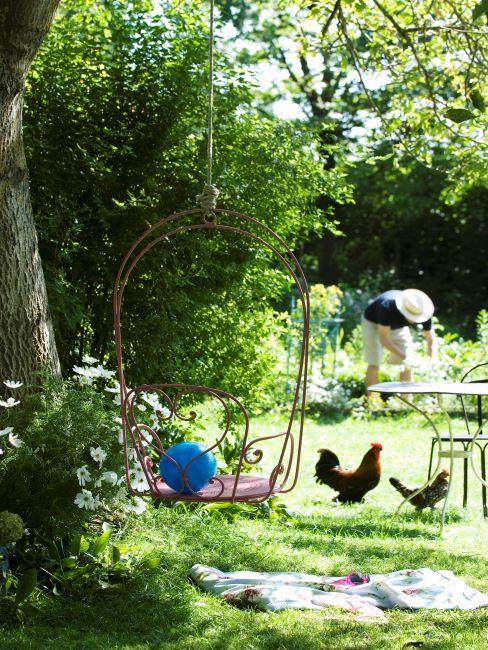 Fauteuil suspendu en métal, style rustique dans un jardin