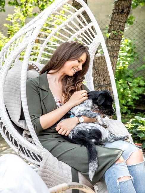 Femme brune avec chien assis dans un fauteuil suspendu blanc