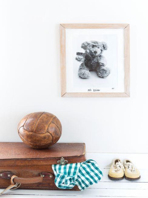 Couloir avec balle, chaussures, caleçon vichy et cadre avec image d'ours