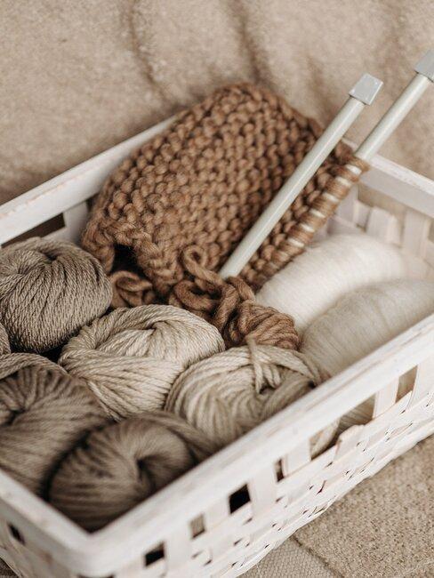 cagette remplie de pelotes de laines et d'aiguilles a tricoter