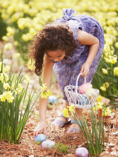 Petite fille cherchant des œufs de Pâques dans le jardin