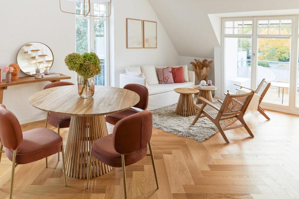 arrière plan zoom avec salon avec table ronde en bois, chaises couleur terre, canapé blanc