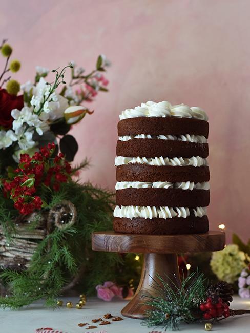 layer cake au chocolat sur un présentoir à pied et avec bouquet de fleurs