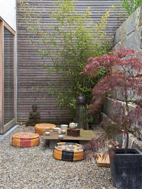 Jardin style zen avec table basse en bois et coussins de sol de couleurs différentes, et arbres plantés dans des pots
