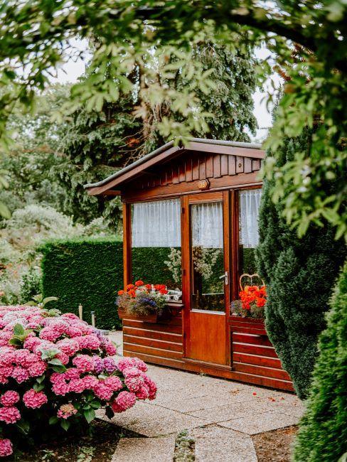 Abri de jardin en bois laqué avec rideaux et fleurs dans jardinières