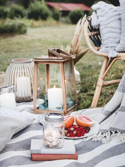Pique-nique sur l'herbe avec une lanterne de jardin en bois avec bougies sur plaid
