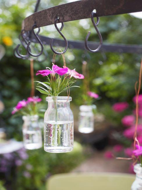 Fleurs roses dans de petits pots récup suspendus sur un un présentoir fait main