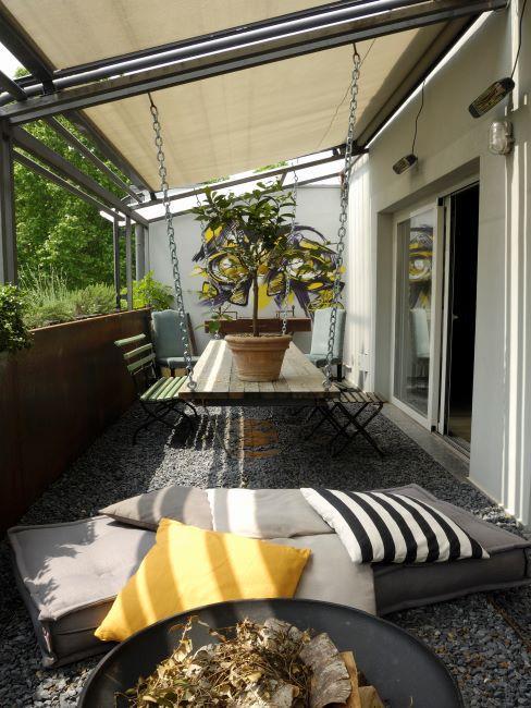 Mobilier extérieur en bois avec coussins décoratifs divers et plantes de balcon