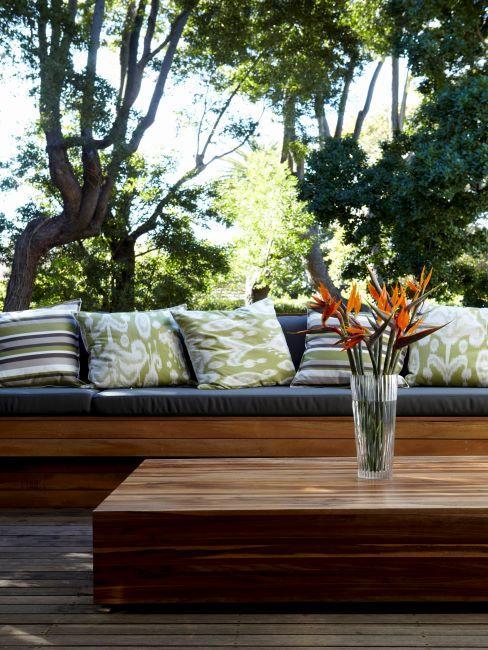 terrasse avec sol en bois, table basse en bois avec vase et canapé extérieur