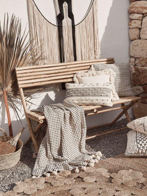 coin extérieur avec banc en bois, plaid beige et coussins déco