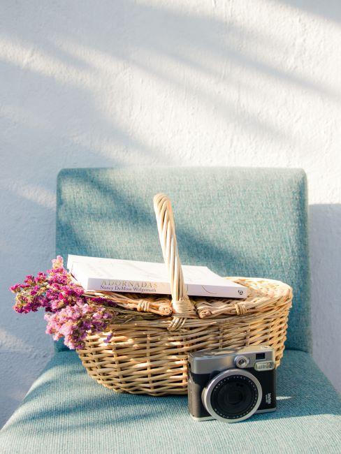 panier pose sur une chaise bleue pale rempli des fleurs, un livre pose dessus, un appareil photo a cote