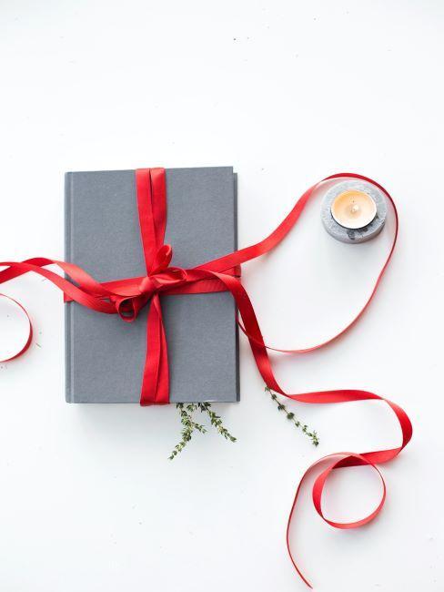un livre gris decore d un ruban rouge sur plan blanc