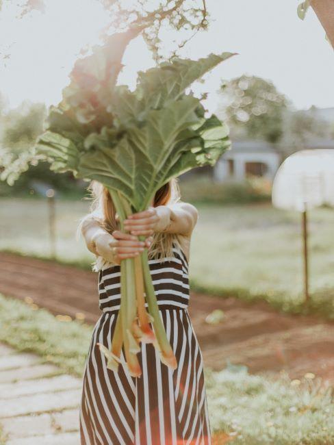 femme qui tend un bouquet de grandes feuilles vertes
