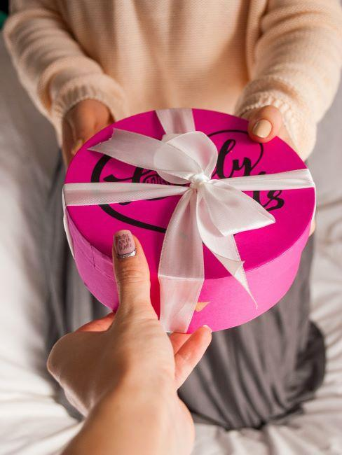 une main de femme offrant une boite ronde rose vif a une autre femme dont on ne voit que les mains