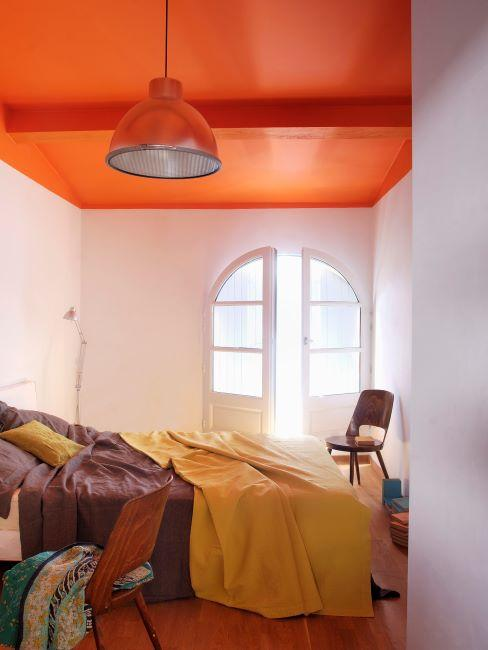 Chambre a coucher avec plafond orange et accessoires deco bruns