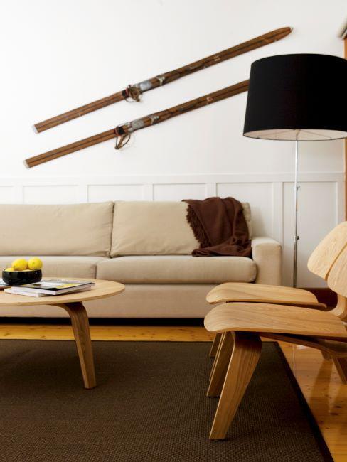 Canape beige avec lampadaire noir, chaises et table basse en bois clair et tapis brun
