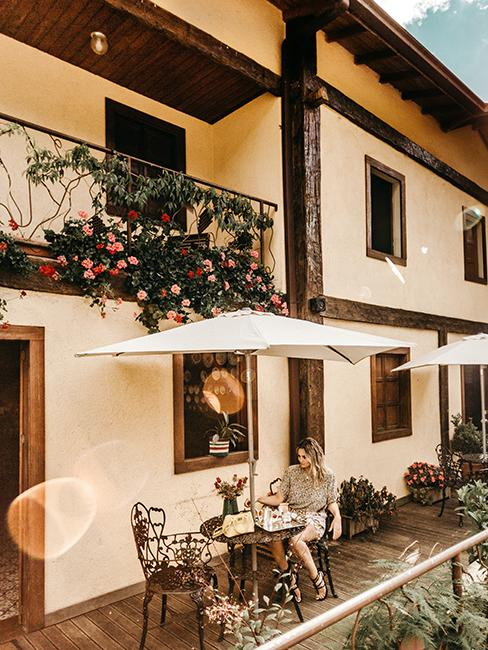 Terrasse avec personne entrain de prendre un café assise sous un parasol et un balcon fleuri au dessus