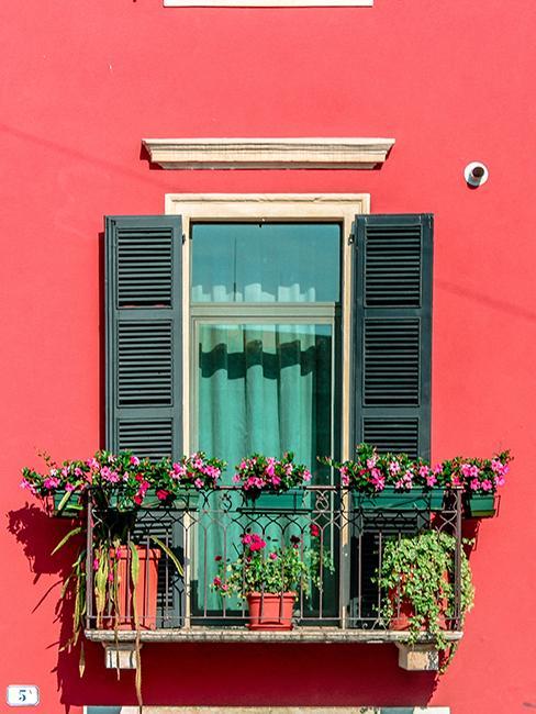 petit balcon fleuri avec jardinière et façade rose