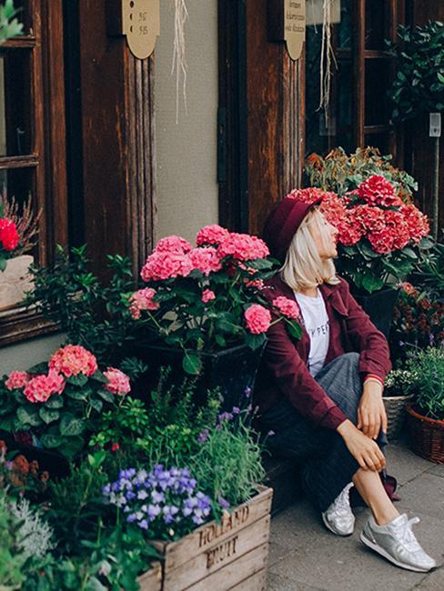 personne assise sur le pas de la porte avec pleins des fleurs autout