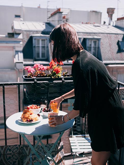 personne entrain de préparer son petit dejeuner sur un balcon fleuri