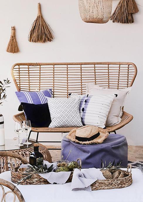 banc de jardin en polyrotin avec coussins boho, pouf bleu et table basse en rotin