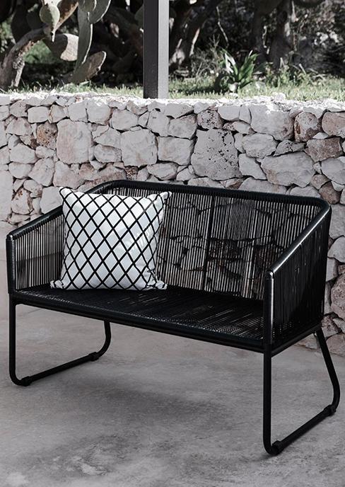 banc de jardin en plastique tressé noir avec coussin graphique et mur en pierre