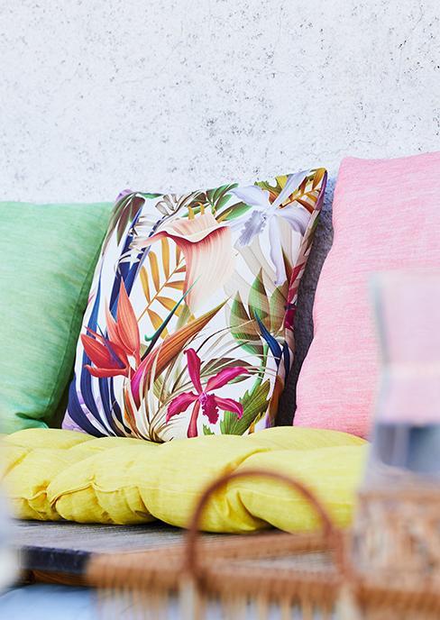 coussins décoratifs colorés sur banc de jardin
