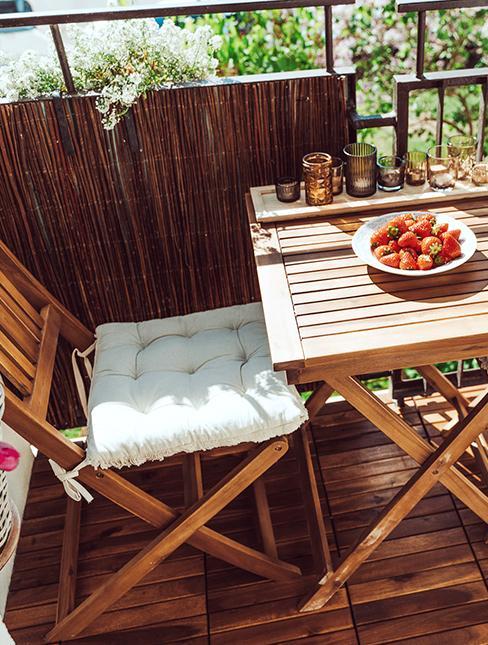 balcon avec canisse, table et chaise en bois