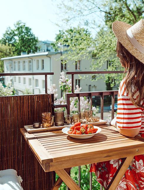 personne entrain de prendre son petit déjeuner sur le balcon avec une table en bois et des canisses