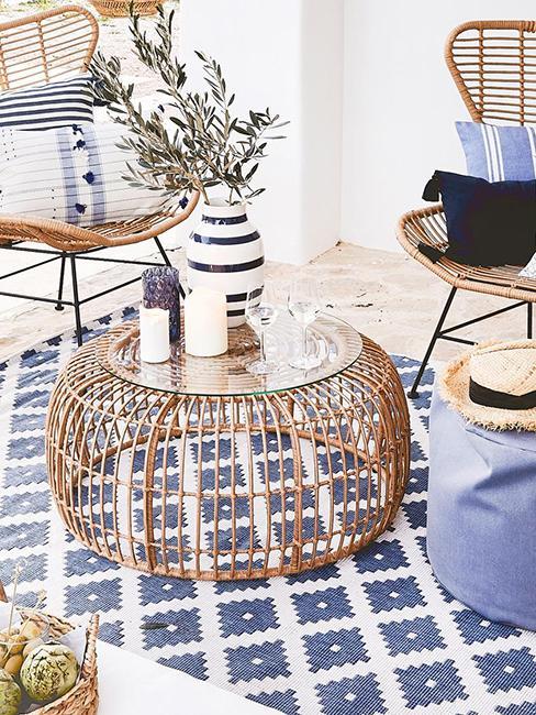 table basse ronde en rotin pour la terrasse avec tapis bleu exterieur