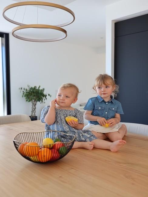 Deux filles de Lola Rossi assises sur l'ilot de la cuisine