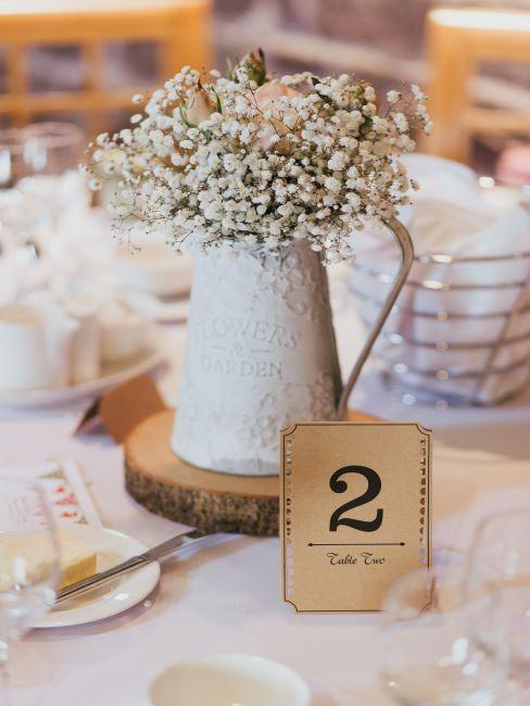 Fleurs dans un pichet vintage avec carton marqueur de table en métal doré