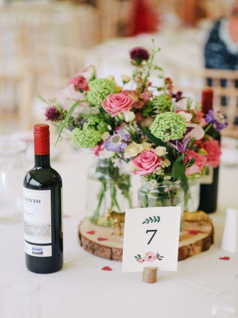 Table avec carton de table, bouteille de vin rouge et bouquet de fleurs