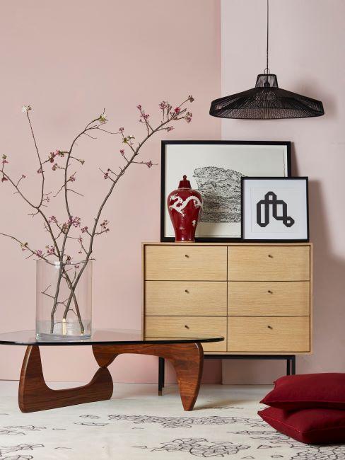 Interieur de style japonais avec commode en bois clair, table basse, branches avec fleurs et decorations