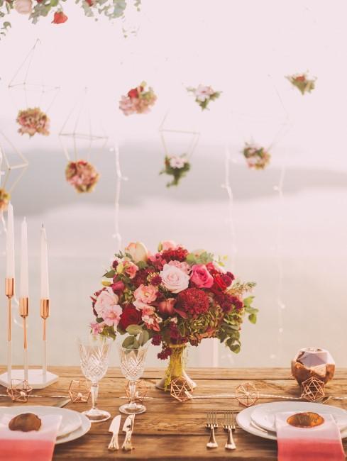 décoration de mariage avec table en bois,, chandelier et bouquet de fleurs roses