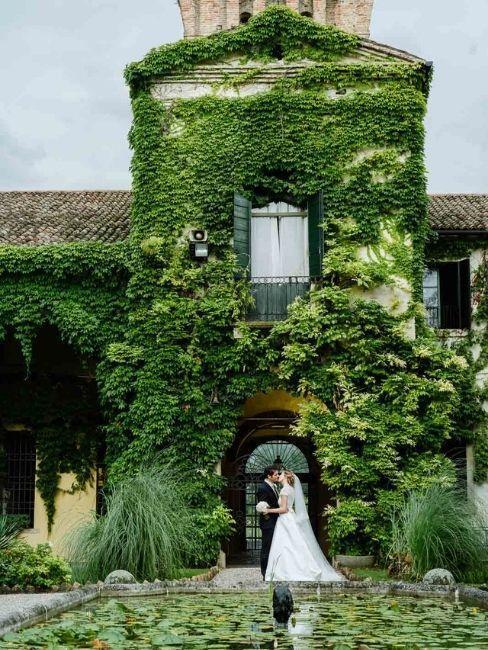 mariage dans un château avec couple de mariés devant un mur végétal