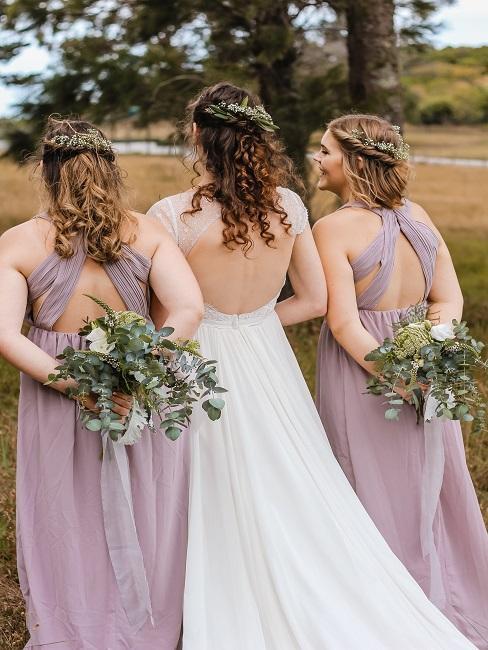 marié en blanc avec ses demoiselles d'honneur en rose de dos